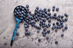 Garden blueberries on a concrete background with vintage wooden spoon. Top view Royalty Free Stock Photos