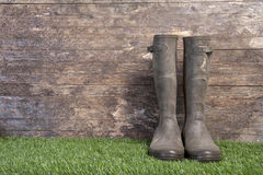 Garden boots on grass against a wooden wall Royalty Free Stock Images