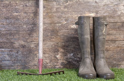 Garden boots and rake on grass Stock Image