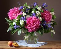 Garden bouquet of peonies, irises and Jasmine in a vase. Garden bouquet of peonies, irises and Jasmine in a glass jug. Still life with flowers in a vase Stock Photo
