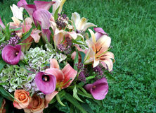 Garden bouquet set on green grass. Calalilies, roses, day lilies, and hydrangea in a beautiful bouquet Royalty Free Stock Photo