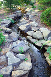 The Garden Brook. A brook lined with stones winds through a garden Royalty Free Stock Photography