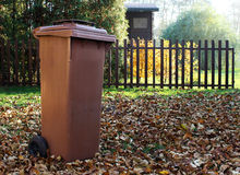 Garden with brown dustbin for autumn fallen leaves. Photo of garden with brown dustbin for autumn fallen leaves royalty free stock image