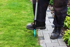 Garden care. Man edging lawn Royalty Free Stock Photo