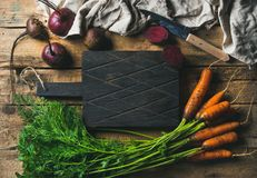 Garden carrots and beetroots with dark cutting board in center stock photography