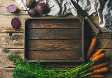 Garden carrots and beetroots with wooden tray in center royalty free stock images