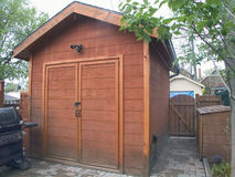 Garden Cedar Tool Shed. A two-door garden cedar tool shed in an urban back yard stock image