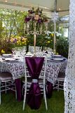 Garden Celebration. Luxurious table set with purple and silver textiles, stemware, china, in a garden setting under a lit tent Stock Photo