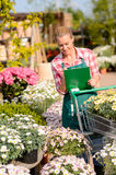 Garden center woman check flowers write notes Royalty Free Stock Photography