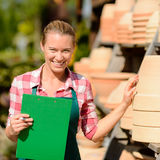 Garden center woman by clay pots shelf Stock Images