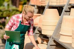 Garden center woman looking down clay pots Stock Image