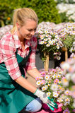 Garden center woman looking down potted flowers Stock Photography