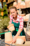 Garden center woman putting clay pots cart Royalty Free Stock Images