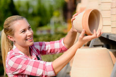 Garden center woman putting clay pots shelf Royalty Free Stock Images