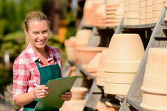 Garden center woman standing by clay pots Stock Photos