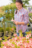 Garden center woman write notes potted flowers Stock Photos