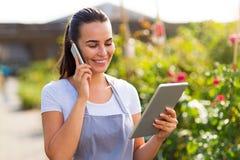 Garden center worker using digital tablet. Smiling employee in garden center Royalty Free Stock Photos