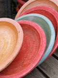 Garden ceramics 3. Stack of coloured flower plates on a wooden table Stock Images