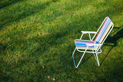 Garden chair on green lawn background Royalty Free Stock Image