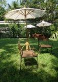 Garden chair on green lawn under the white umbrella Stock Photos