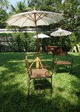 Garden chair on green lawn under the white umbrella. Light on garden chair on green lawn under the white Stock Photos