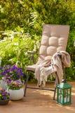 Garden chair on terrace in sunlight, flowers  bush Stock Photos