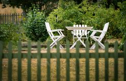 Garden chairs and table behind fence Royalty Free Stock Photos