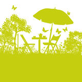 Garden chairs with umbrella in the garden Stock Images