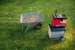 Garden chipper, electric shredder mulcher with wheelbarrow full of wooden mulch stock images