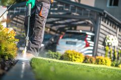 Garden Cleaning Work. With Powerful Pressure Washer. Cleaning Cobble Stone Path Elements stock images