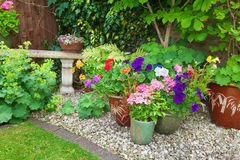 Garden with containers full of colorful flowers Royalty Free Stock Image