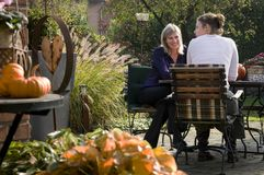 Garden conversation. Two woman having conversation at the garden table with autumn decoration Royalty Free Stock Images