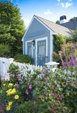 Garden cottage. New England garden cottage surrounded by flowers Stock Photos