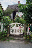 Garden cottage with gate. Cute cottage in a garden with a small gate stock images