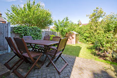 Garden with dark wooden furniture. Rear garden in summer time with wooden furniture and shed royalty free stock image