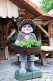 Garden decoration. Wooden man with basket full of flowers Stock Photo