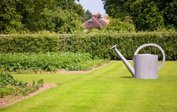 Garden decoration. Big watering can on the lawn Royalty Free Stock Photography