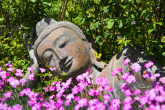 Garden decoration with a lying buddha. Stock Photos