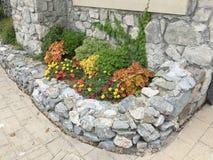 Garden design around rock house Stock Image