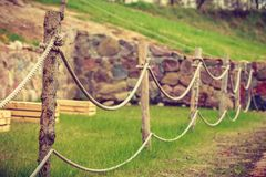 Old fashioned fence made of sticks and cord. Garden design concept. Old fashioned fence made of sticks and cord, outdoor shot Stock Photo