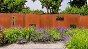 Garden design with a rusted garden screen. Garden design with a modern rusted metal garden screen and purple salvias royalty free stock photo