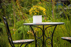 Garden with desk and bouquet of flowers Stock Photo