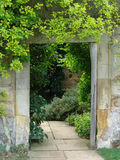 Garden doorway with path. Walled garden entrance with path and shrubs stock photography