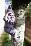 Garden Dwarf. Observer decoration climbing on a tree Stock Photos