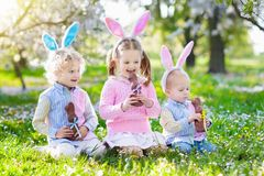 Garden Easter egg hunt. Kids eat bunny chocolate. Stock Photography