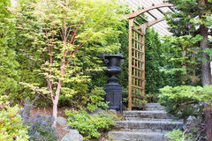 Garden Entrance with Arbor and Stone Steps. Garden Entrance with Arbor Stone Steps Urn Pot and Trees Royalty Free Stock Photo