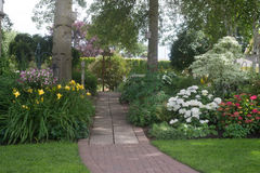 Garden Entrance. A beautifully designed brick walkway leads into a back yard perennial garden stock photos