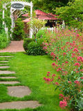 Garden entry with path and flowers. An informal path leads through grass to a gated garden patio with red umbrellas and flowers in bloom located in Jacksonville Royalty Free Stock Images