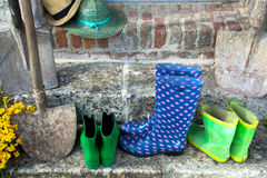 Garden equipment - rubber boots, schovels and srtaw hats in sunny day. On old stone wall background royalty free stock images