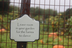 Garden fairies. White plaque hanging on fence in garden Royalty Free Stock Image